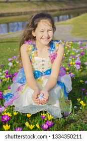 Easter happy child portrait. Pretty little girl holds Easter chocolate eggs among spring flowers. Cute smiling child looks for chocolate Easter eggs.