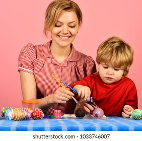 Easter and happy moments concept. Family prepares for holiday on pink background. Mother and son painting eggs for Easter. Woman and little boy with smiling faces making decorations.