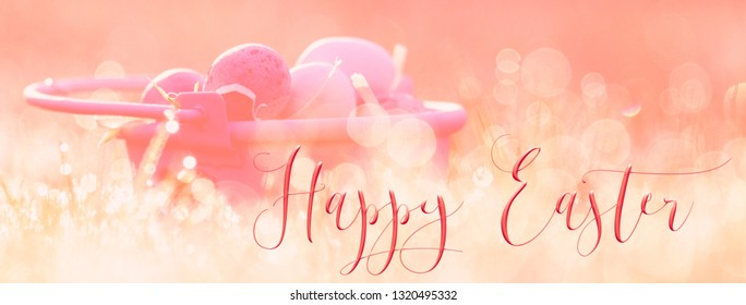 Easter header, background, with Mini easter eggs in a little pink bucket in the grass. Great for social media campaigns.