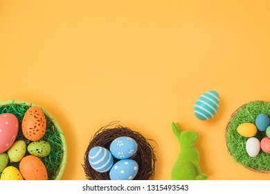 Easter holiday background with easter eggs in basket and bunny decoration. Top view from above. Flat lay