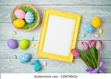 Easter holiday background with easter eggs in basket, photo frame and tulip flowers on wooden table. Top view from above