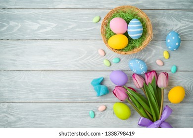 Easter holiday background with easter eggs in basket and tulip flowers on wooden table. Top view from above