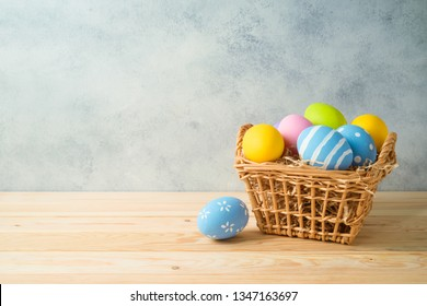 Easter holiday background with easter eggs in basket  on wooden table