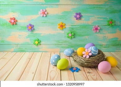 Easter holiday background with easter eggs in bird nest and paper flowers on wooden table