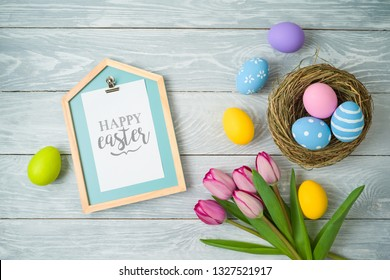 Easter holiday background with easter eggs in bird nest, note and tulip flowers on wooden table. Top view from above