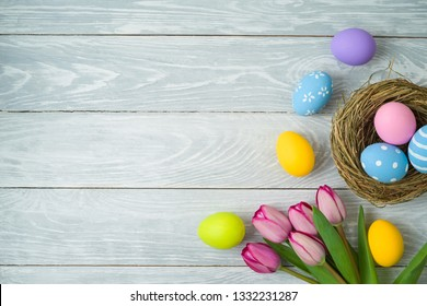 Easter holiday background with easter eggs in bird nest and tulip flowers on wooden table. Top view from above