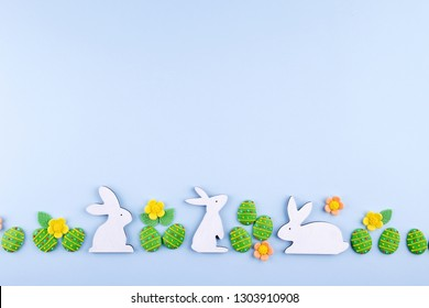 Easter holiday background. Green sugar candy eggs, wooden bunny on blue background. Flat lay, top view