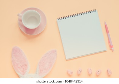 Easter holiday background with notebook and pen, cup for coffee, bunny ears and easter eggs. Copy space background. Flat lay. Toned