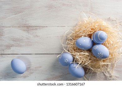 Easter holiday background with painted eggs on white wooden boards, copy space