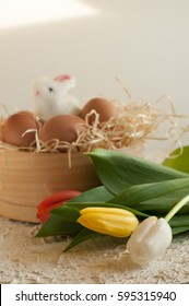 Easter holiday basket with eggs, flowers and easter bunny on rustic wooden Easter rabbit with eggs tulips