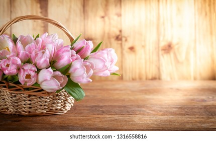 Easter holiday basket with pink tulips on wooden background in rustic style.