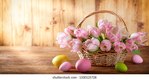 Easter holiday basket with pink tulips and Easter eggs on wooden background in rustic style.
