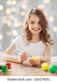 easter, holiday and child concept - close up of girl with brush coloring easter eggs over lights background