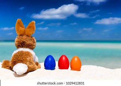 Easter holiday concept: bunny with colored eggs on a tropical beach