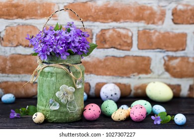 Easter holiday decoration with violet flowers and painted eggs