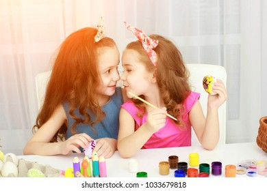 Easter holiday, easter eggs, happy family concept. Cute little sisters painting Easter eggs. Happy family preparing for Easter.