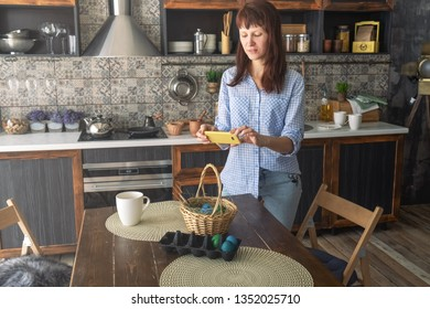 Easter holiday: a girl photographs on a smartphone a basket with colored eggs on the kitchen table.
