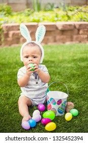 Easter Holiday lifestyle photo. Cute little boy trying to swallow a plastic Easter egg he found while on an Easter egg hunt outdoors in the yard.