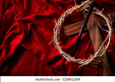 Easter holiday, reminder of the sacrifice of the Lord and Savior Jesus Christ concept with wooden cross, crown of thorns and rusty Crucifixion nail isolated on a red velvet background with copy space
