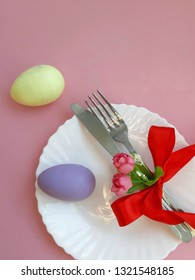 Easter holiday table setting. Fork, knife with red bowknot, white plate on pink background. Selective focus. Place for text.