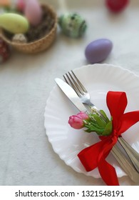 Easter holiday table setting. Fork, knife with red bowknot, white plate on fabric background. Selective focus. Place for text.