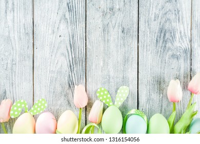 Easter holiday table setting with rabbits and eggs, plates with colorful eggs and chocolate bunny rabbits, festive ribbon, wooden background top view copy space