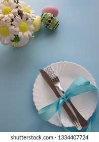 Easter holiday table setting. Silverware with blue bowknot on plate, bouquet of flowers, decorated eggs on light blue background. Top view. Place for text.