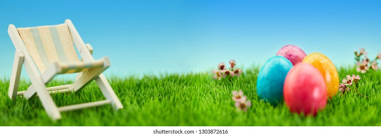 Easter holidays concept with easter eggs and deck chair on a green meadow