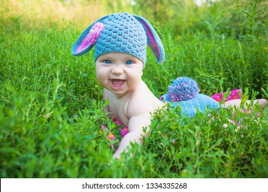 Easter holidays for happy kids. Cute baby in rabbit of lamb costume in the green spring grass. Smiling baby kid posing like an Easter bunny. Children have fun.