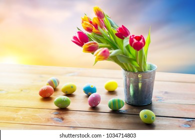 easter, holidays, tradition and object concept - close up of colored eggs and tulip flowers in bucket on wooden table over sky background