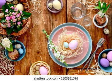 Easter home decor concept, overhead view on rustic wooden table decorated for Easter dinner
