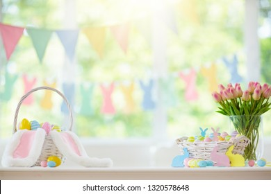 Easter home decoration. Basket with colorful dyed eggs and rabbit ears, tulip flowers and wooden bunny for festive Easter celebration at home. Kids basket for Easter egg hunt.