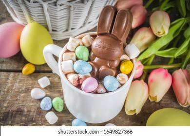 Easter hot chocolate with chocolate bunny rabbits. easter eggs and marshmallow, wooden background with spring flowers copy space