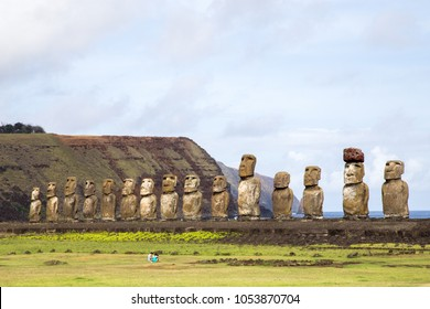 Easter Island, Chile - December 3, 2015: Two tourists sitting in front of the 15 moais at Ahu Tongariki