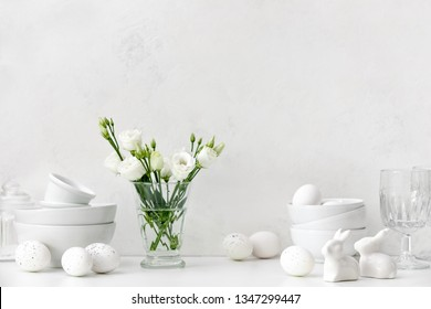 Easter kitchen table decorated with Easter eggs, ceramic rabbits and flowers, home white tableware on a kitchen table, front view, blank space for a text