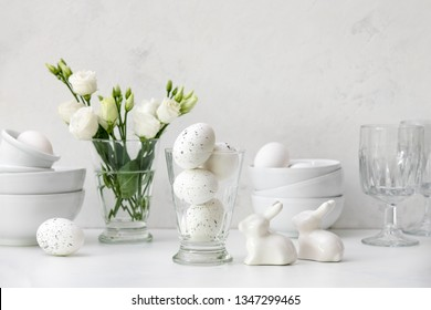 Easter kitchen table decorated with Easter eggs, ceramic rabbits and flowers, home white tableware on a kitchen table, front view