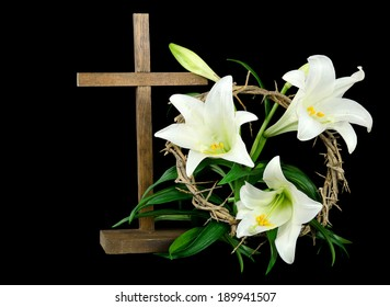 Easter lily with wooden cross and crown of thorns on a black background