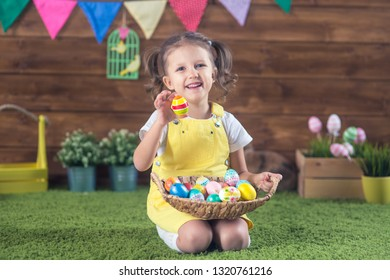 Easter. Little girl child in easter bunny ears with colored eggs on wooden background