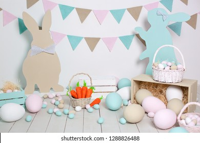 Easter! Many colorful Easter eggs with bunnies and baskets! Easter decoration of the room, children's room for games. Basket with carrots and rabbits. Easter photo shoot. Nest, eggs, boxes of hay.