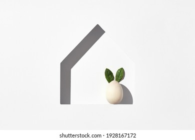 Easter minimal background with house silhouette and eggs. Sunshine with harsh shadow. Happy easter 2021 creative concept. Flat lay, top view