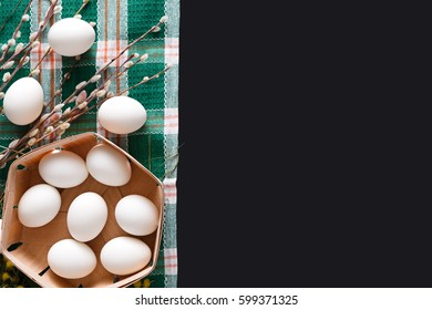 Easter mockup. White eggs unpainted, pattern for your colors, in basket on napkin at black background decorated with pussy willow spring flowers. Top view with copy space