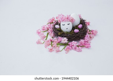easter nest of beautiful pink hyacinth flowers with a chicken eggs on a white backgrorund. Easter composition. Horizontal frame. Free space for text