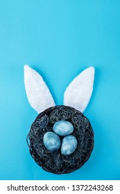 Easter nest with blue eggs on a color background. Festive wreath with decor.