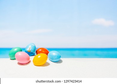 Easter on tropical beach background. Eggs on the white sand. Vacation and travel concept in spring