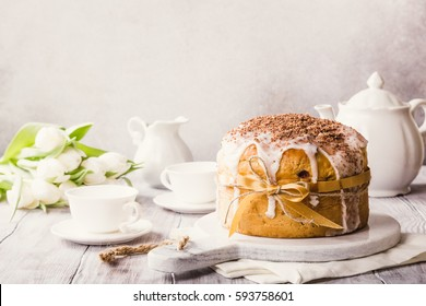 Easter orthodox sweet bread, kulich and colorful quail eggs with white tulips. Holidays breakfast concept with copy space. Retro style toned.