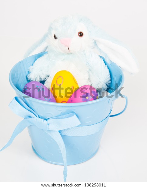 Easter Pail filled with toys, eggs, and candy. Isolated on a white background.