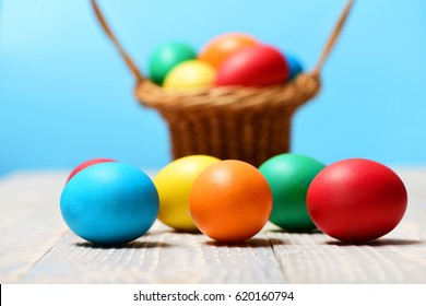 easter painted colorful handmade eggs on wood in basket on blurred blue background, happy holiday celebration, traditional food