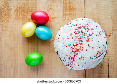 Easter painted eggs and cake on wooden backdrop. Top view.