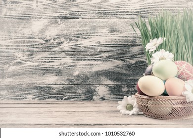 Easter painted eggs and flowers on wooden rustic table, vintage holiday wallpaper