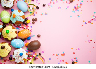 Easter party concept with easter eggs, cupcakes, chocolate, candies, confetti on a pink packground. Top view, copy space